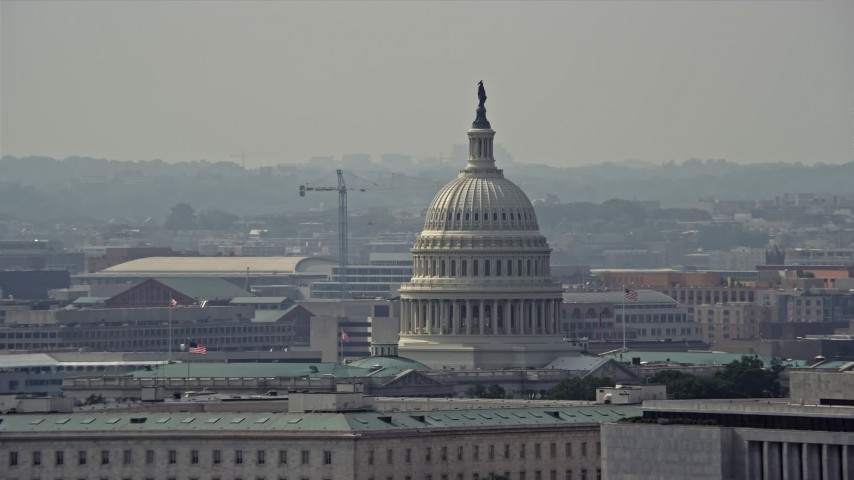 5K stock footage aerial video of the United States Capitol dome behind the James Madison Building in Washington DC Aerial Stock Footage | AX75_069E