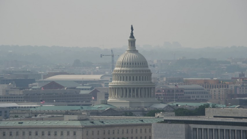 5K stock footage aerial video of the dome of the United States Capitol seen over rooftops in Washington DC Aerial Stock Footage | AX75_070