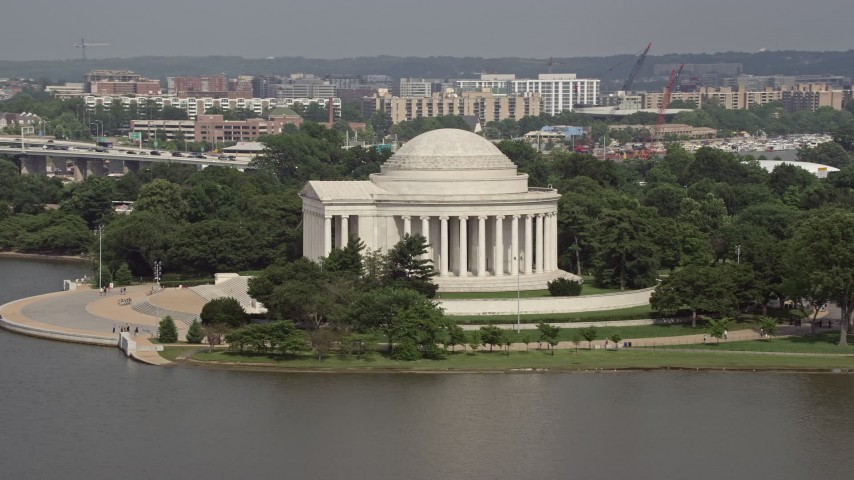 5K stock footage aerial video flying by the Jefferson Memorial, revealing the Jefferson Statue inside in Washington DC Aerial Stock Footage | AX75_086