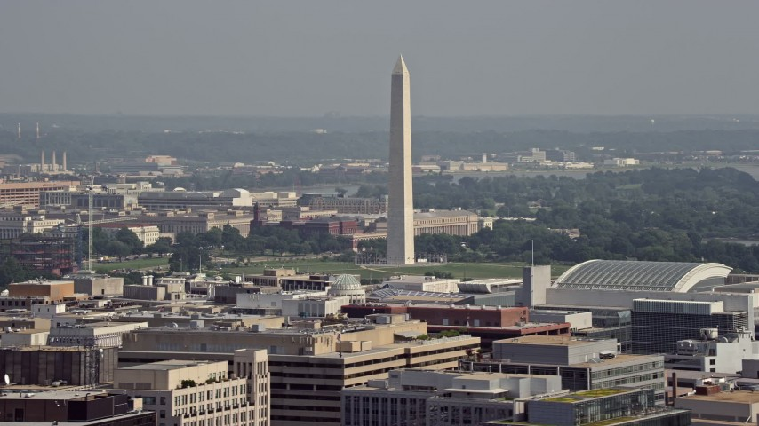 5K stock footage aerial video of the Washington Monument seen from office building rooftops in Washington DC Aerial Stock Footage | AX75_095
