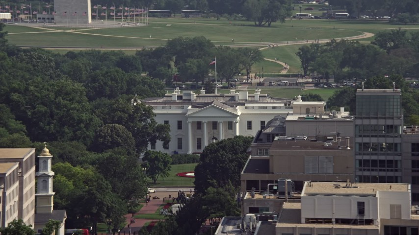 5K stock footage aerial video of the White House seen over office building rooftops, reveal Washington Monument in Washington DC Aerial Stock Footage | AX75_111E