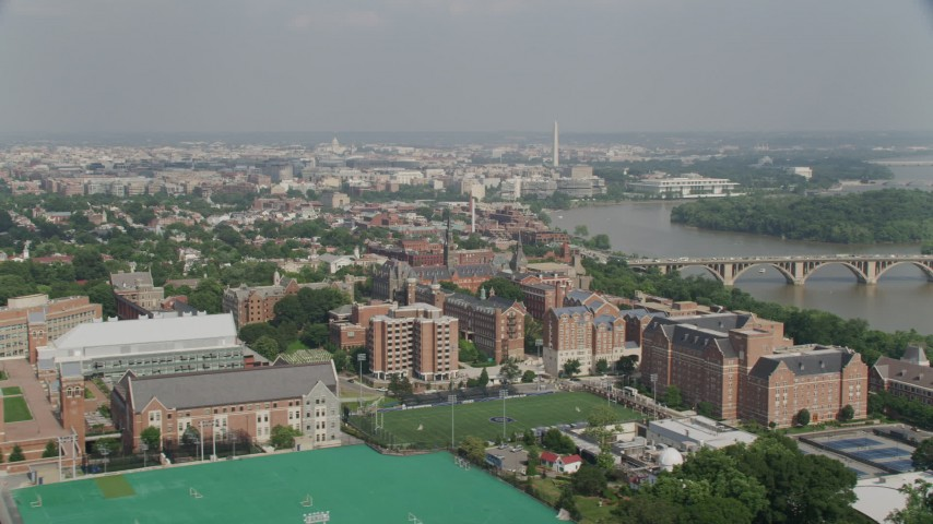 5K stock footage aerial video of Washington Monument, Francis Scott Key Bridge, and Potomac River seen from Georgetown University in Washington DC Aerial Stock Footage AX75_120 | Axiom Images