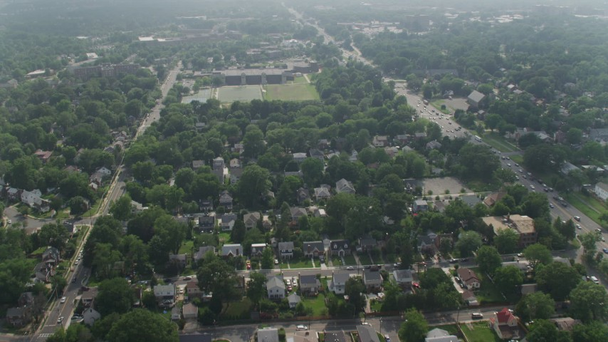 5K stock footage aerial video flying over suburban homes to approach an elementary school in Arlington, Virginia Aerial Stock Footage | AX75_140