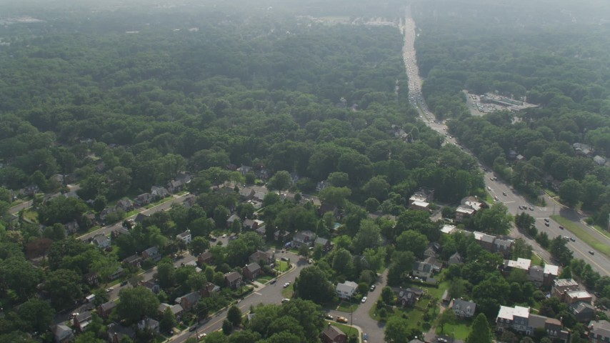 5K stock footage aerial video flying over suburban Arlington, Virginia neighborhoods and trees beside Highway 50 Aerial Stock Footage | AX75_144