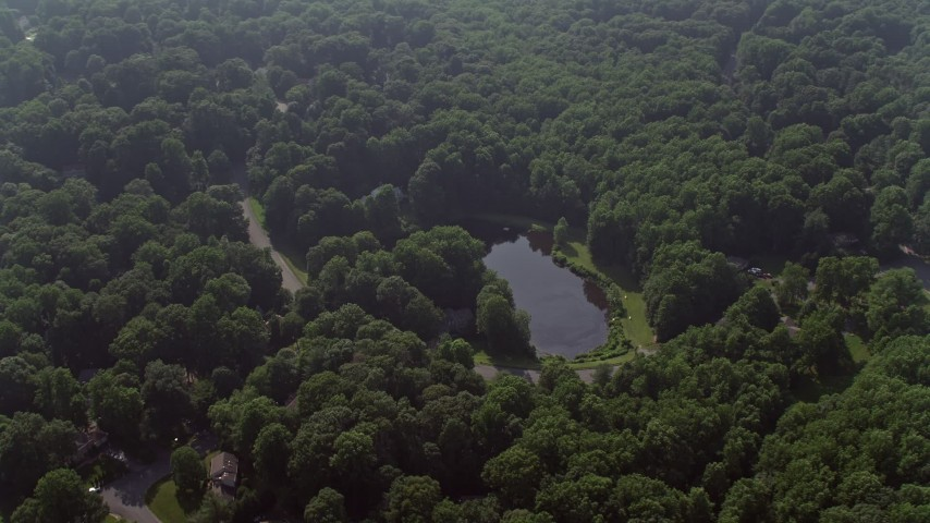 5K stock footage aerial video of homes by pond on Havenner Road, surrounded by forest in Fairfax Station, Virginia Aerial Stock Footage | AX75_165
