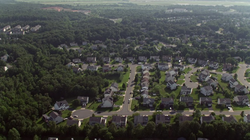 5K stock footage aerial video flying over suburban homes to approach warehouse buildings in Manassas, Virginia Aerial Stock Footage | AX75_175
