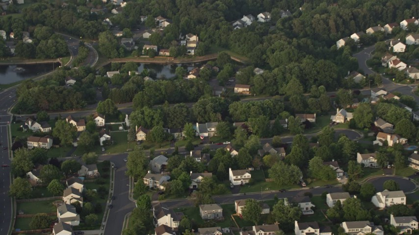 5K stock footage aerial video tilting to bird's eye view of suburban homes in Manassas, Virginia, sunset Aerial Stock Footage | AX76_003