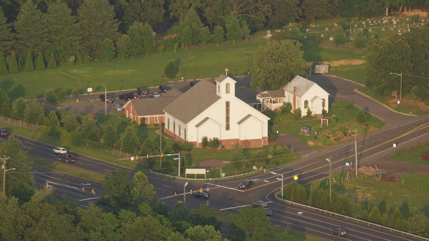 5K stock footage aerial video of Buckhall United Methodist Church on the corner of a busy intersection, Manassas, Virginia, sunset Aerial Stock Footage   AX76_005