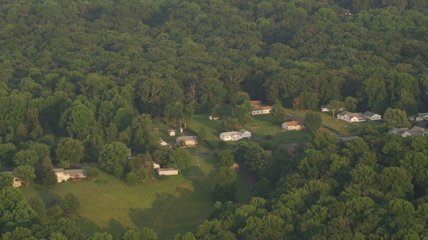 5K stock footage aerial video flying by rural homes near forest, Manassas, Virginia, sunset Aerial Stock Footage | AX76_007