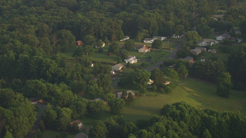 5K stock footage aerial video flying by rural homes near forest, Manassas, Virginia, sunset Aerial Stock Footage | AX76_008