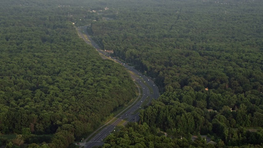 5K stock footage aerial video flying by Ox Road, dense forest, Fairfax Station, Virginia, sunset Aerial Stock Footage | AX76_014