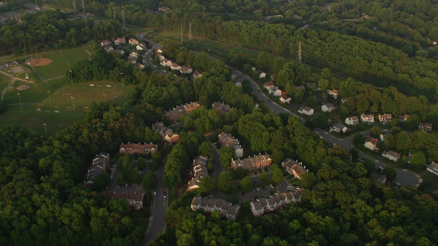 5K stock footage aerial video flying over town houses, power lines, trees, and row houses in Springfield, Virginia, sunset Aerial Stock Footage | AX76_017