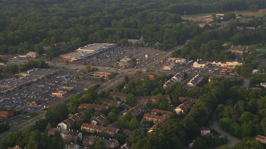 5K stock footage aerial video flying by town houses near strip malls, Springfield, Virginia, sunset Aerial Stock Footage | AX76_019