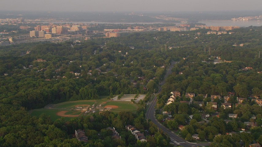 5K aerial video flying over baseball fields, suburban neighborhoods, Alexandria, Virginia, sunset Aerial Stock Footage | AX76_026