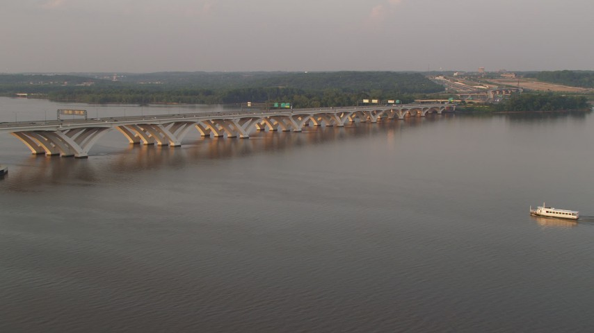5K stock footage aerial video of ferry near Woodrow Wilson Memorial Bridge, Potomac River, Fort Washington, Maryland, sunset Aerial Stock Footage | AX76_032