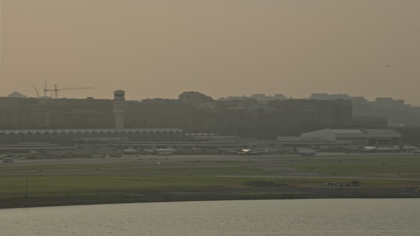 5K stock footage aerial video flying by Ronald Reagan Washington National Airport, Arlington, Virginia, sunset Aerial Stock Footage | AX76_038