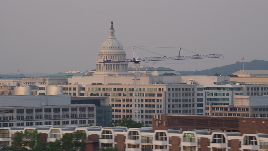 5K aerial video flying by United States Capitol dome and office buildings, Washington D.C., sunset Aerial Stock Footage | AX76_045