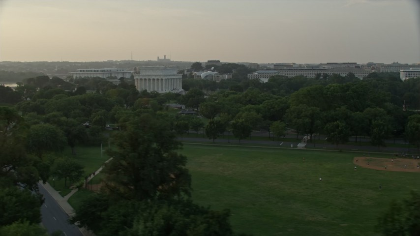 5K aerial video flying by Lincoln Memorial, seen from West Potomac Park, Washington D.C., sunset Aerial Stock Footage | AX76_049