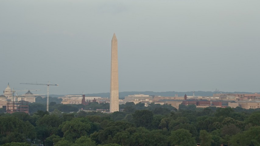 5K stock footage aerial video of the Washington Monument, reveal the United States Institute of Peace, Washington D.C., sunset Aerial Stock Footage | AX76_052