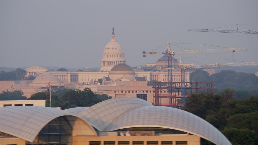 5K aerial video flying by United States Capitol, Smithsonian Museum domes, and cranes, Washington D.C., sunset Aerial Stock Footage | AX76_056