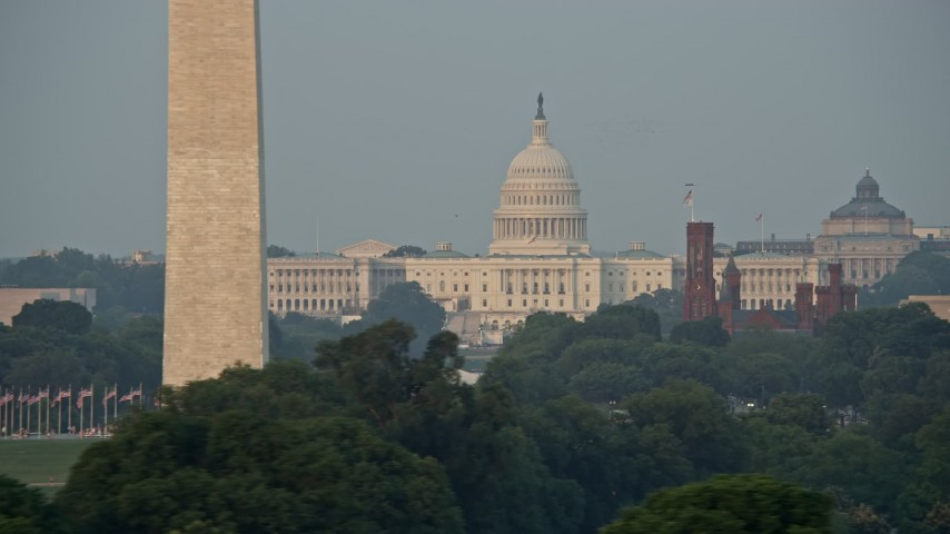 5K stock footage aerial video flying by United States Capitol, Smithsonian Museum domes, and cranes, Washington D.C., sunset Aerial Stock Footage   AX76_056E