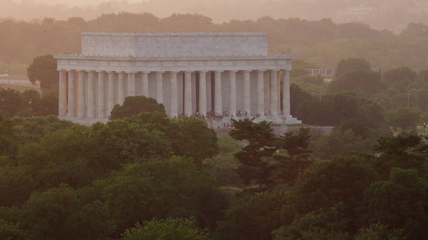 5K stock footage aerial video flying by Lincoln Memorial with tourists on the steps, Washington D.C., sunset Aerial Stock Footage | AX76_067