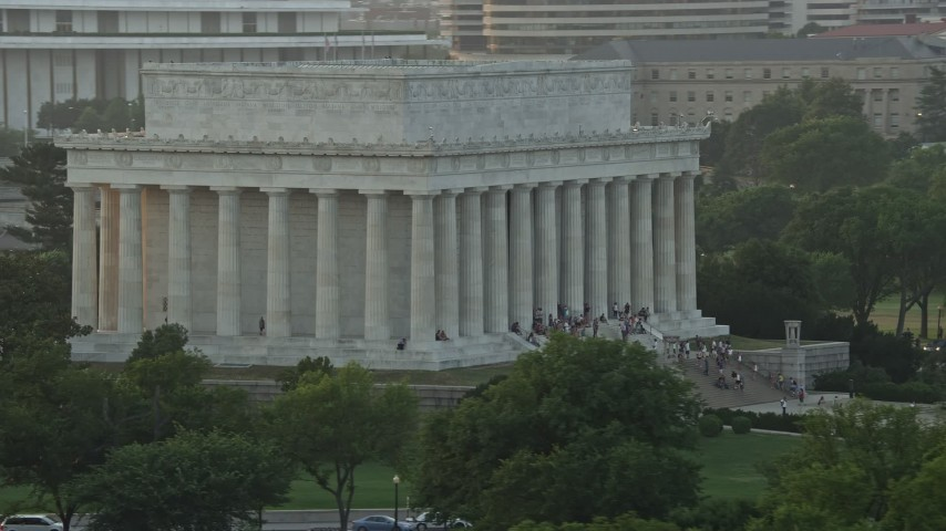5K stock footage aerial video flying by Lincoln Memorial with tourists on the steps, Washington D.C., sunset Aerial Stock Footage   AX76_067E