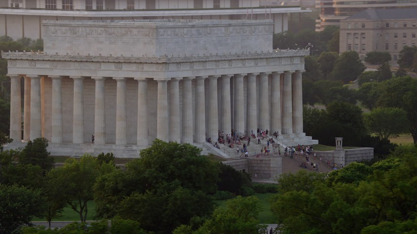 5K stock footage aerial video flying by the south side of the Lincoln Memorial with tourists, Washington D.C., sunset Aerial Stock Footage | AX76_068