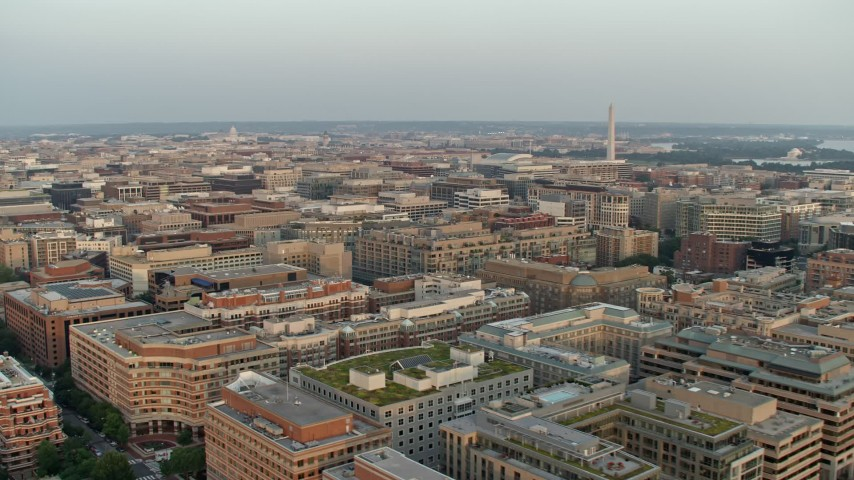 5K stock footage aerial video of the Washington Monument over office and apartment buildings, Washington D.C., sunset Aerial Stock Footage | AX76_075