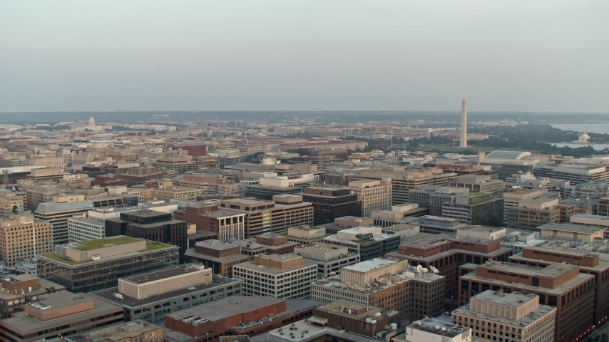 5K aerial video of Washington Monument and Jefferson Memorial from over buildings, Washington D.C., sunset Aerial Stock Footage | AX76_076
