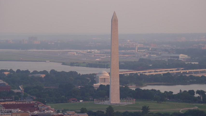 5K stock footage aerial video of Washington Monument and Jefferson Memorial, Ronald Reagan Airport in background, Washington D.C., sunset Aerial Stock Footage | AX76_078