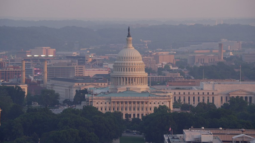 5K stock footage aerial video of the United States Capitol and part of the Rayburn House Office Building in Washington D.C., sunset Aerial Stock Footage | AX76_083
