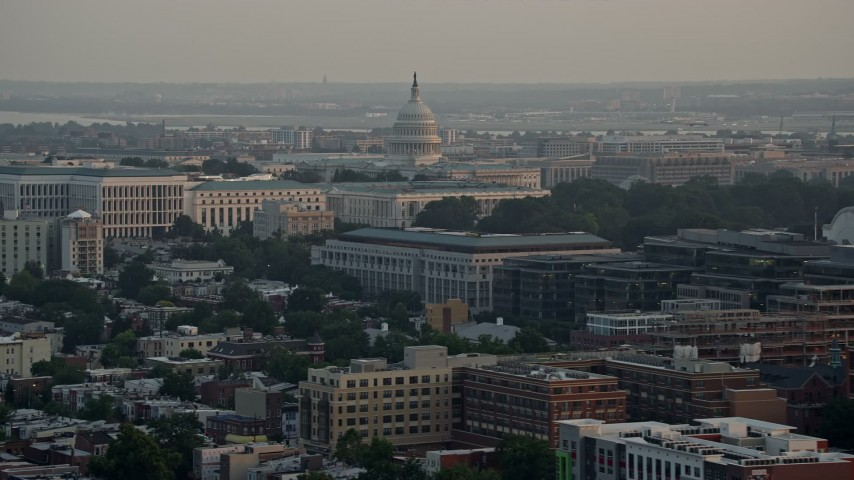 5K stock footage aerial video of the United States Capitol dome behind Senate Office Buildings, Washington D.C., sunset Aerial Stock Footage | AX76_087