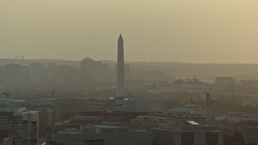 5K stock footage aerial video of the Washington Monument and office buildings in Washington D.C., sunset Aerial Stock Footage | AX76_092