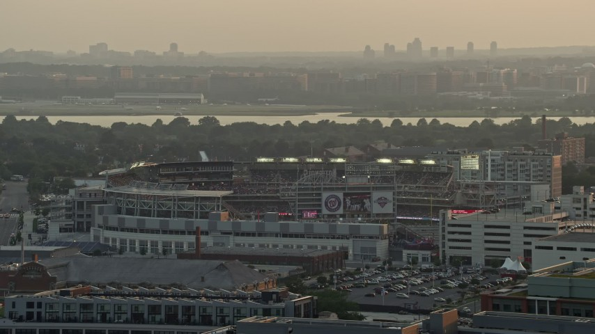 5K stock footage aerial video of Nationals Park, crowded stadium, Ronald Reagan Airport in the background, Washington D.C., sunset Aerial Stock Footage | AX76_093