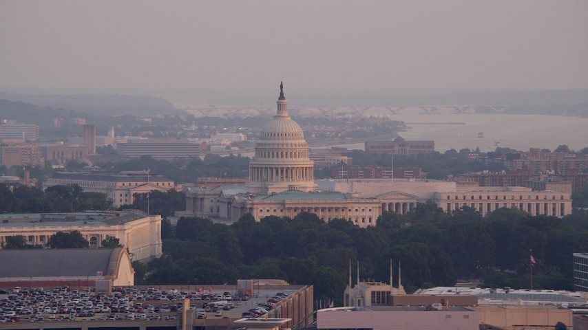 5K stock footage aerial video of the United States Capitol by the Rayburn House Office Building in Washington D.C., sunset Aerial Stock Footage | AX76_101