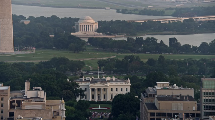 5K stock footage aerial video of the Jefferson Memorial behind the White House, reveal Washington Monument base, Washington D.C., sunset Aerial Stock Footage | AX76_105