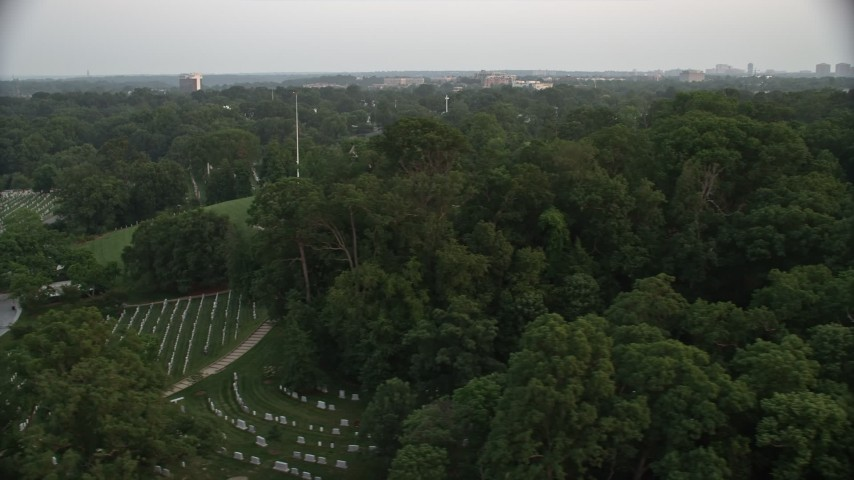 5K stock footage aerial video of gravestones and trees at Arlington National Cemetery, Virginia, twilight Aerial Stock Footage | AX76_116