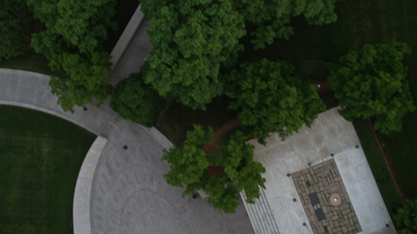5K stock footage aerial video flying over Arlington National Cemetery trees to reveal President John F. Kennedy Gravesite, Virginia, twilight Aerial Stock Footage | AX76_117