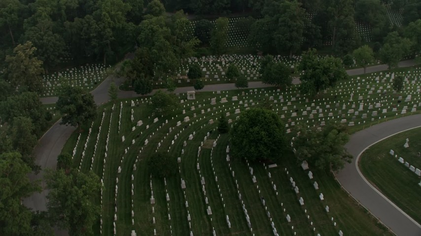 5K stock footage aerial video flying over Arlington National Cemetery, tilt to gravestones, Virginia, twilight Aerial Stock Footage | AX76_118
