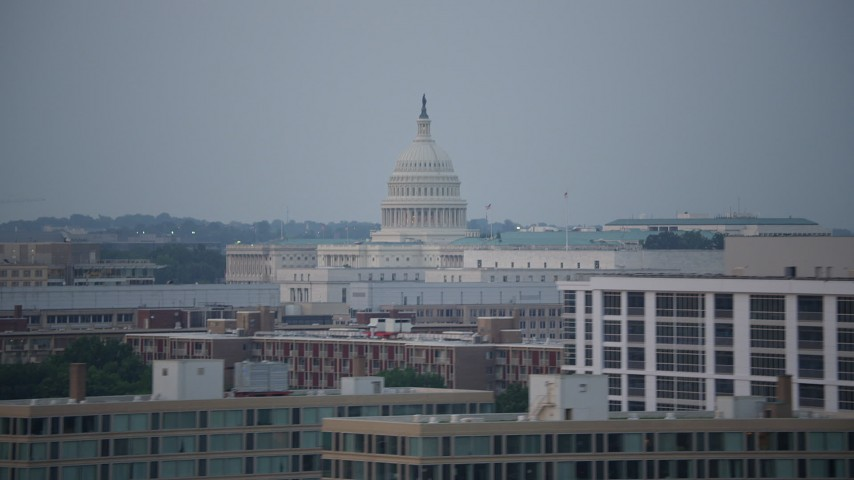 5K stock footage aerial video of the United States Capitol dome behind the Rayburn House Office Building in Washington, D.C., twilight Aerial Stock Footage | AX76_136