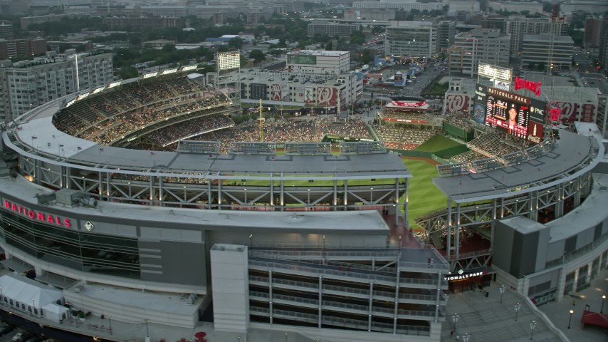 5K stock footage aerial video flying by Nationals Park crowded with fans, Washington, D.C., twilight Aerial Stock Footage | AX76_139