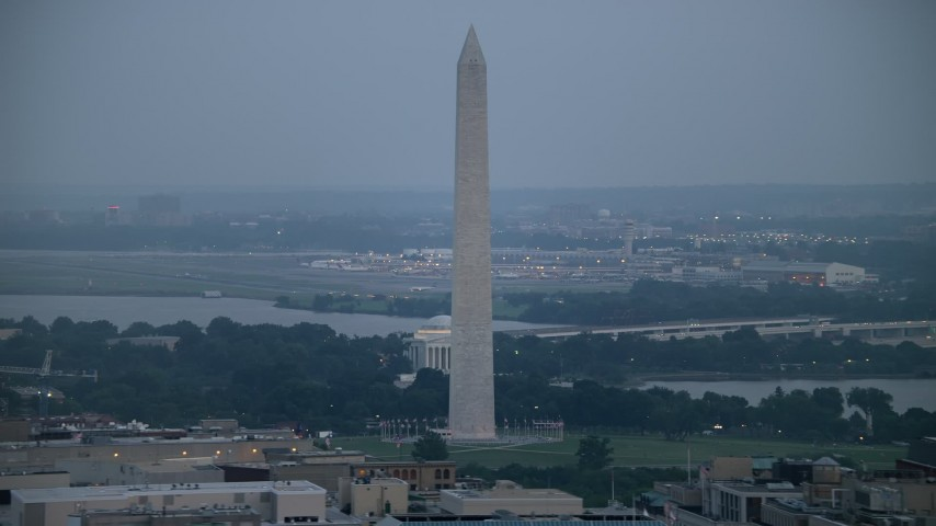 5K aerial video of the Washington Monument, the Jefferson Memorial, and Reagan National Airport in Washington, D.C., twilight Aerial Stock Footage | AX76_159