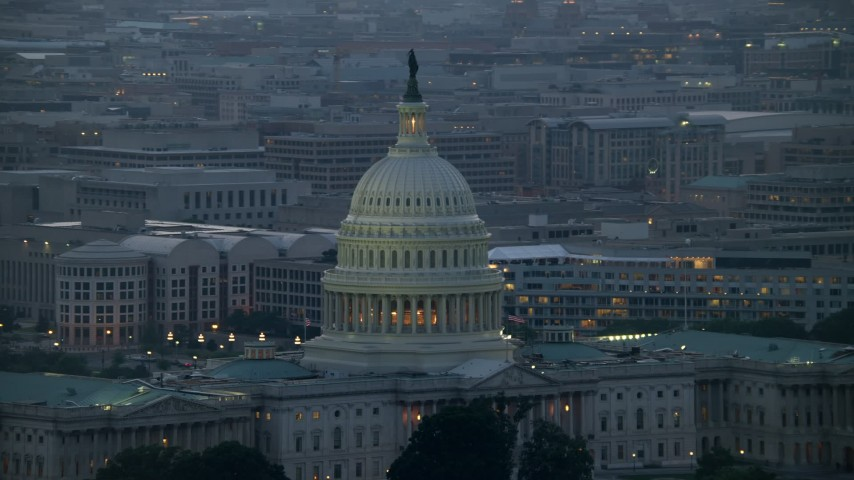 5K stock footage aerial video of the United States Capitol dome, office buildings in background, Washington, D.C., twilight Aerial Stock Footage | AX76_168E