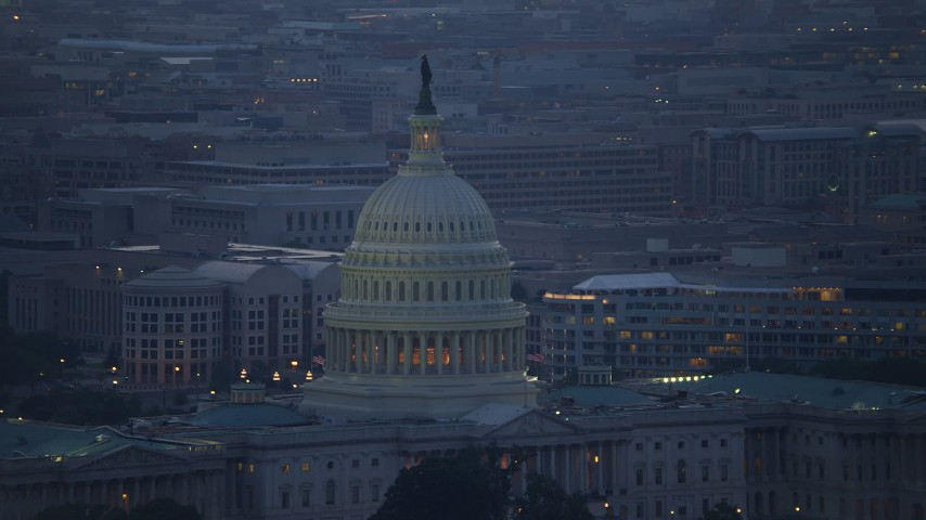 5K stock footage aerial video of the United States Capitol dome, with Washington, D.C. office buildings in the background, twilight Aerial Stock Footage | AX76_169