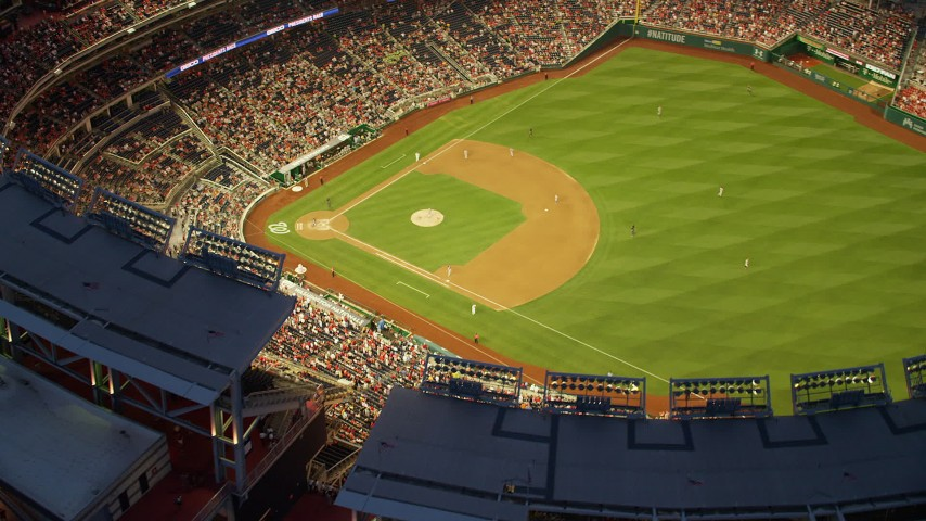 5K aerial video of a reverse view of Nationals Park during a baseball game, Washington, D.C., twilight Aerial Stock Footage | AX76_173