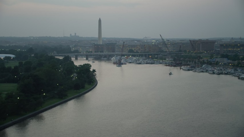 5K stock footage aerial video approaching Washington Monument, Francis Case Memorial Bridge, and marina near office buildings in Washington, D.C., twilight Aerial Stock Footage | AX76_177