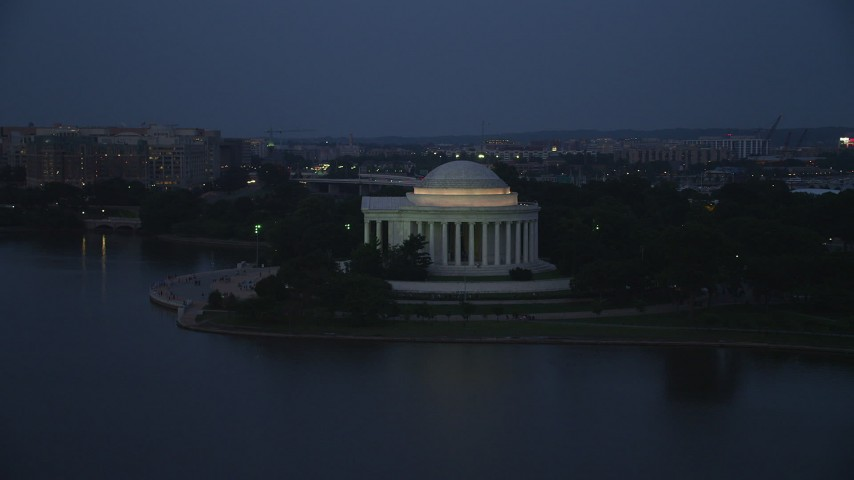 5K stock footage aerial video approaching and flying by the Jefferson Memorial lit up for evening, Washington, D.C., twilight Aerial Stock Footage | AX76_181