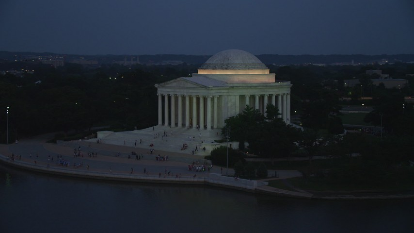 5K stock footage aerial video flying by the front of the Jefferson Memorial lit up for the night, Washington, D.C., twilight Aerial Stock Footage | AX76_182