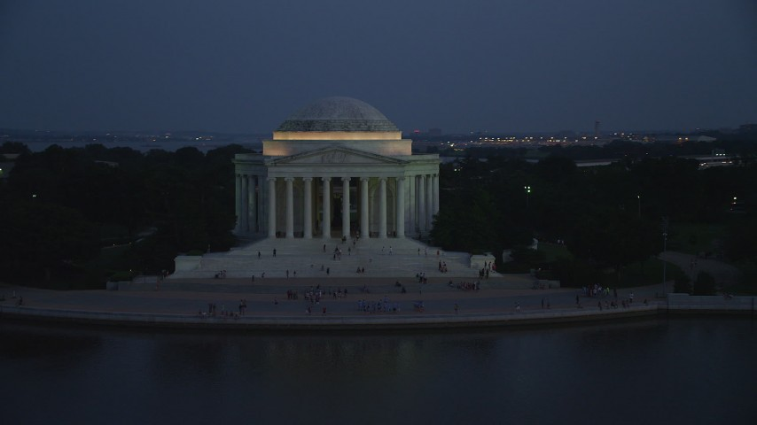 5K stock footage aerial video flying by visitors on the steps of the Jefferson Memorial, lit up for the night, Washington, D.C., twilight Aerial Stock Footage | AX76_183